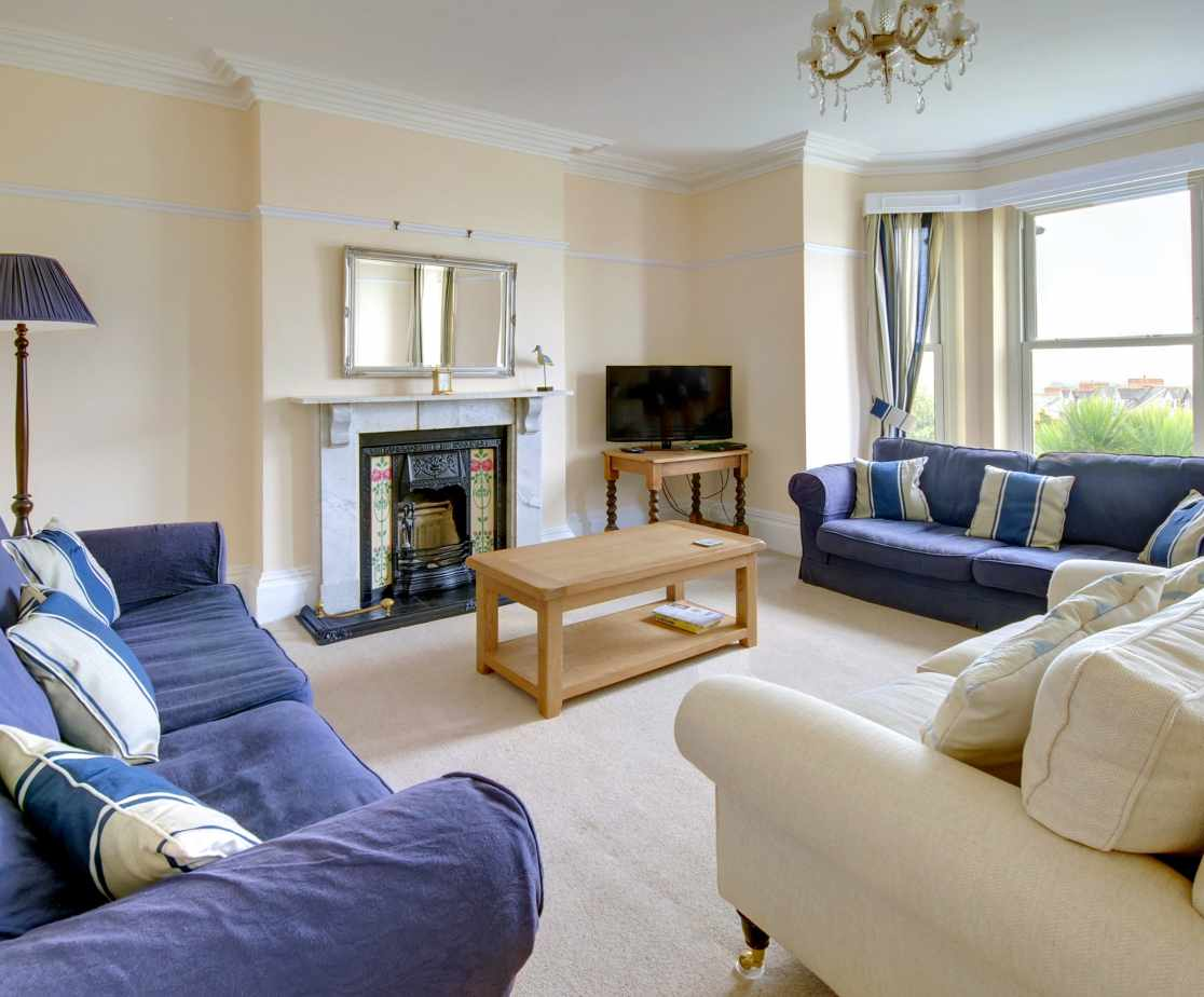 Comfortable seating in the sitting room surrounds the ornate feature fireplace
