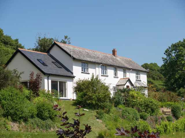 This exceptional detached home enjoys stunning views across the lush green wooded valley and distant sea views from almost every room