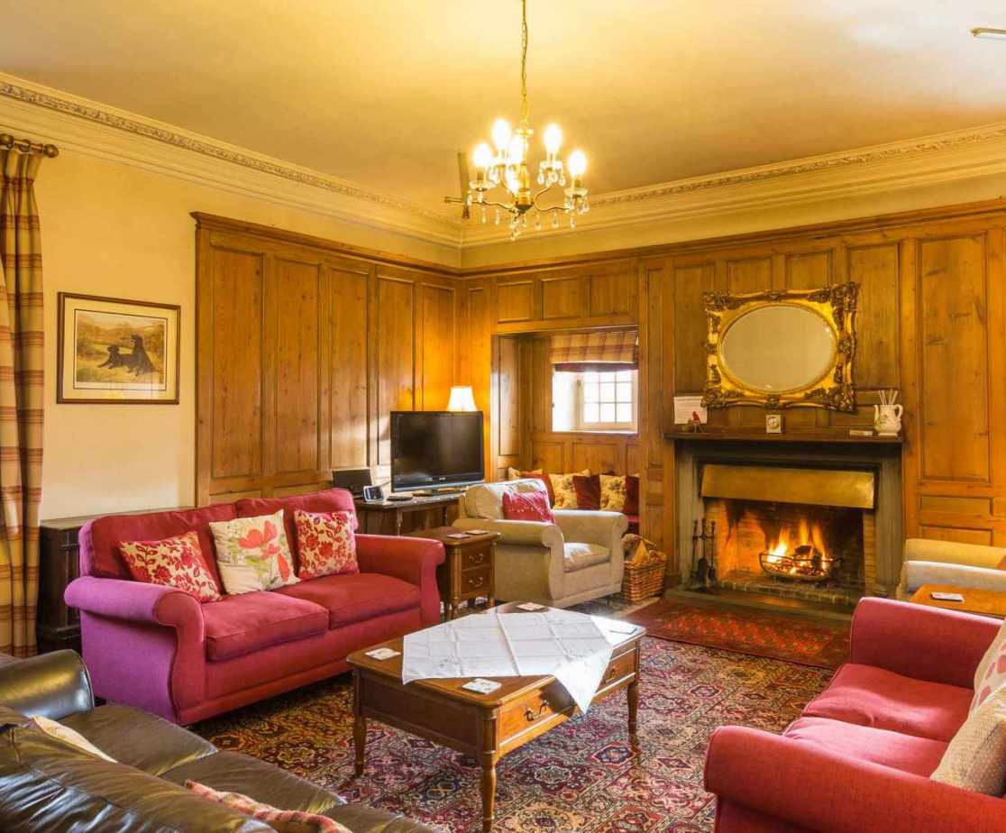 The former Great Hall is located at first floor level and is now the sitting room with an open fire