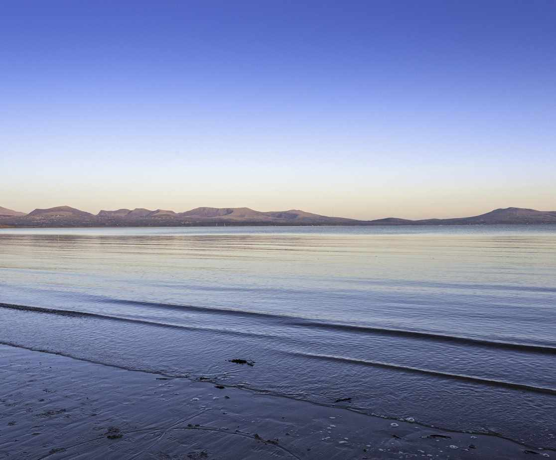 Calm Sea at sunset from Newborough Beach, looking across to Snowdonia