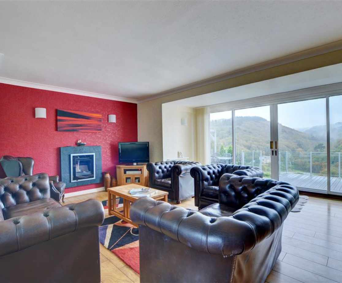 The sitting room has huge French windows leading out to the terrace and comfy Chesterfield leather sofas