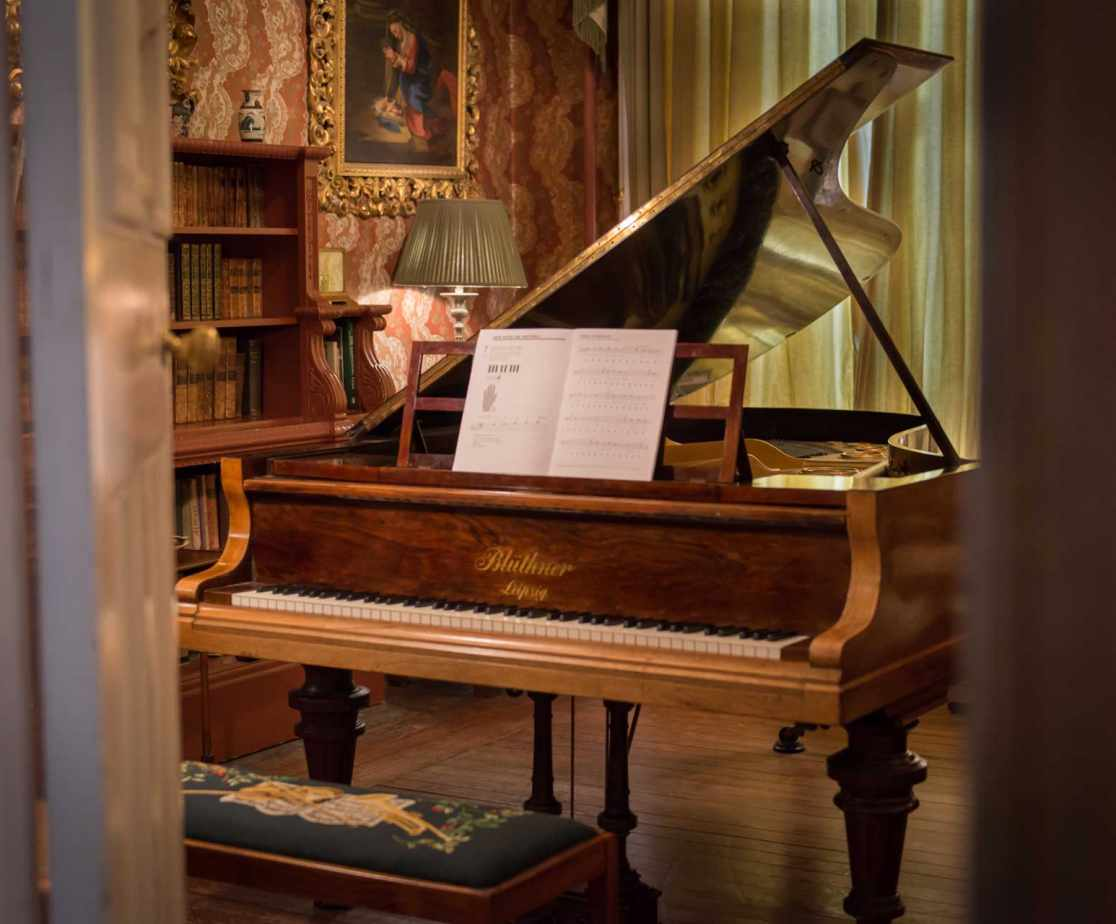 The grand piano awaits in the drawing room