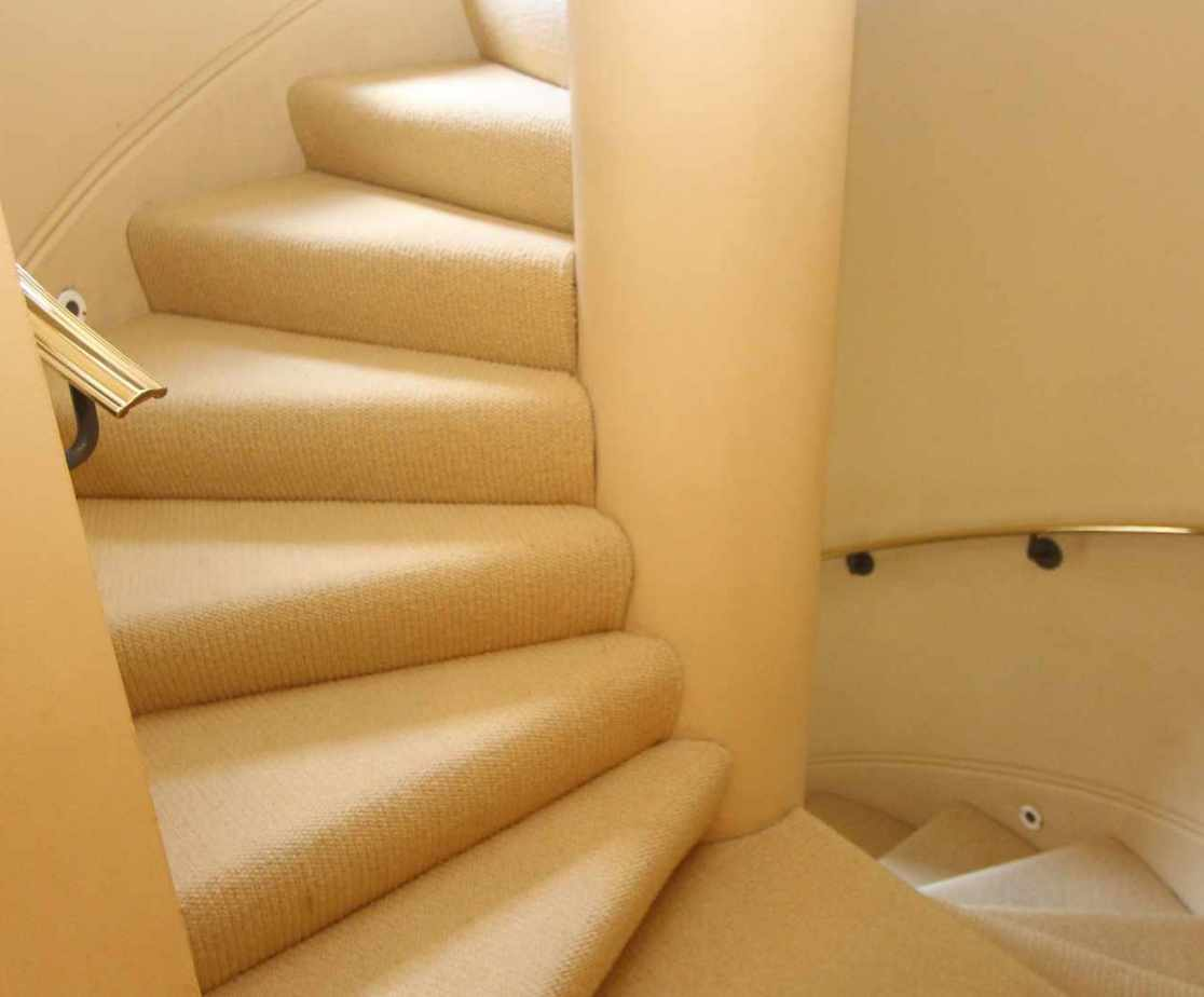 Carpeted spiral stairs lead to the accommodation above