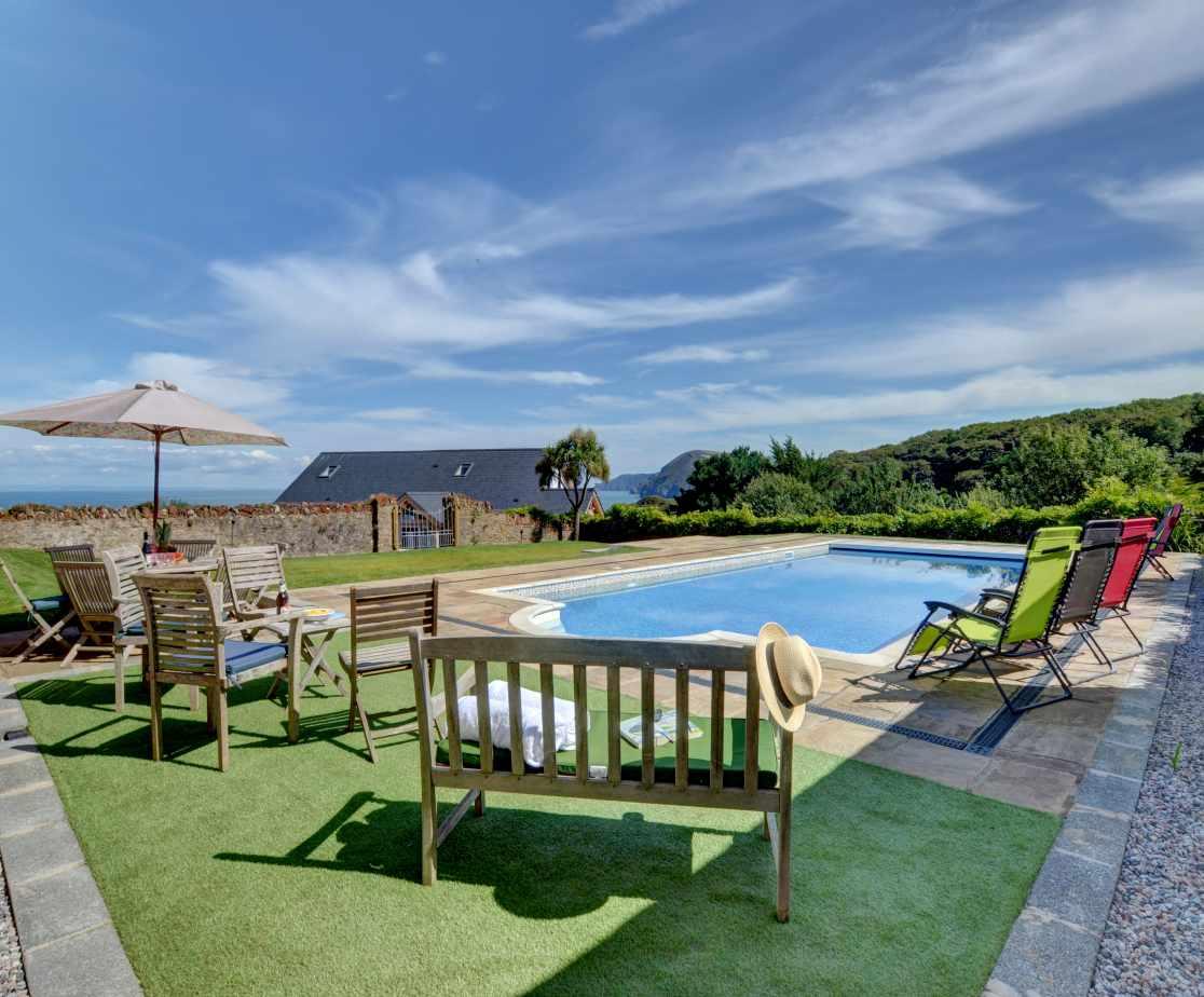 The beautiful swimming pool area with garden furniture