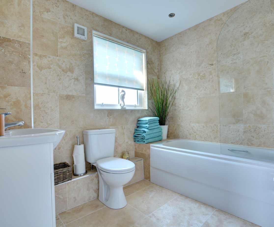 Ground floor family bathroom with bath, overhead shower, toilet and wash hand basin