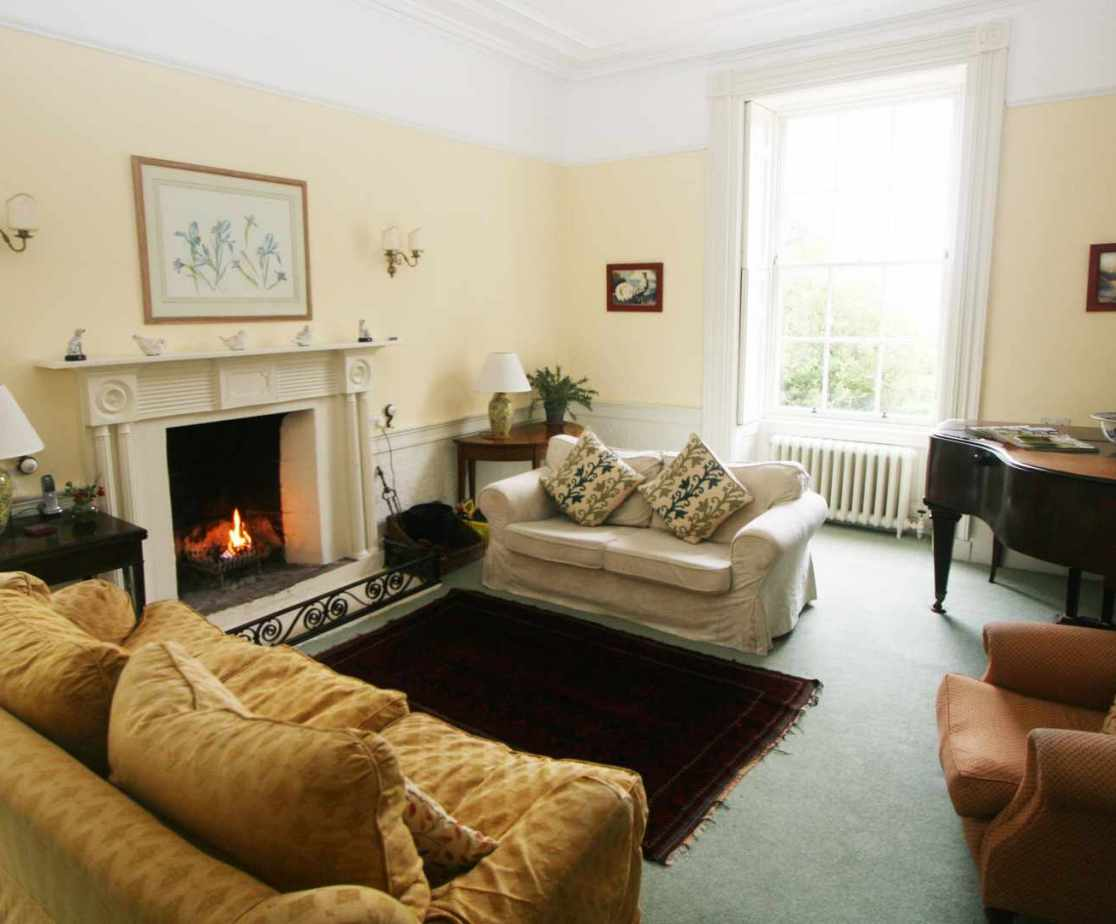 With comfortable sofas and an open fire the drawing room