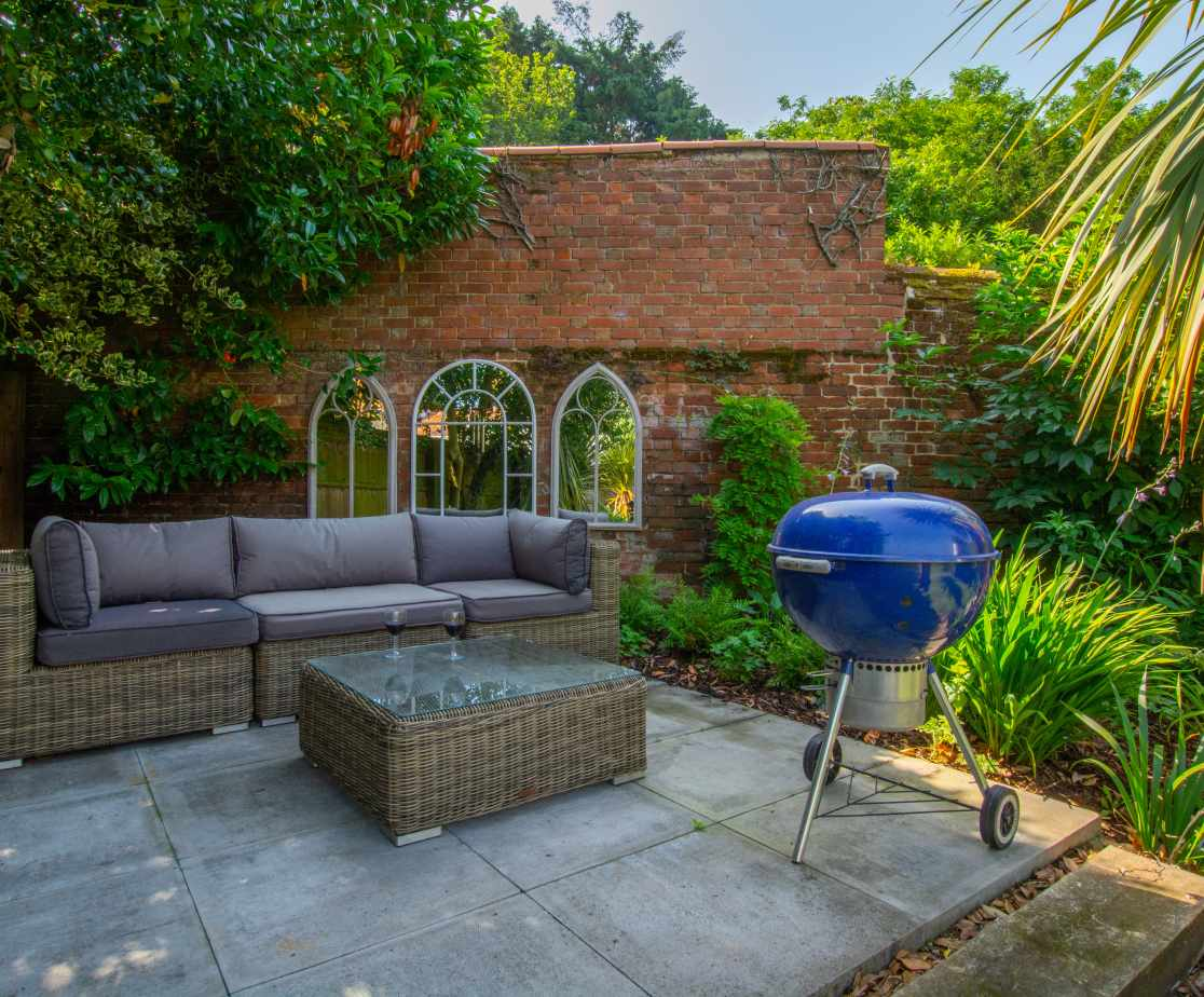 Raised platform in garden with seating and barbeque
