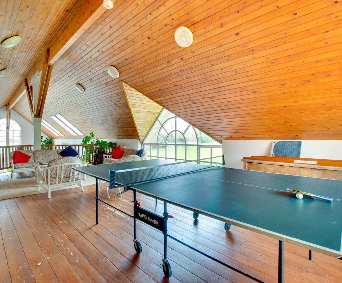 Indoor balcony overlooking pool with conservatory furniture, fridge, table tennis & shuffleboard.