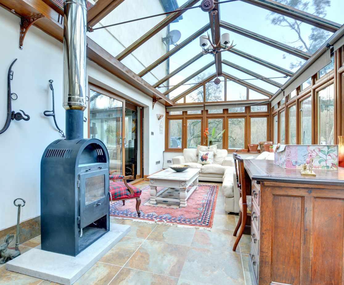 Impressive conservatory, kept warm during the Winter months by wood burner
