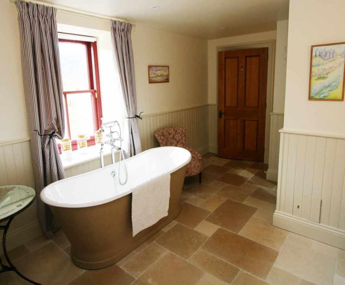 Bedroom 3 en-suite bathroom with a bath with a view